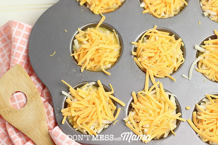 adding cheese to egg mixture in muffin tin