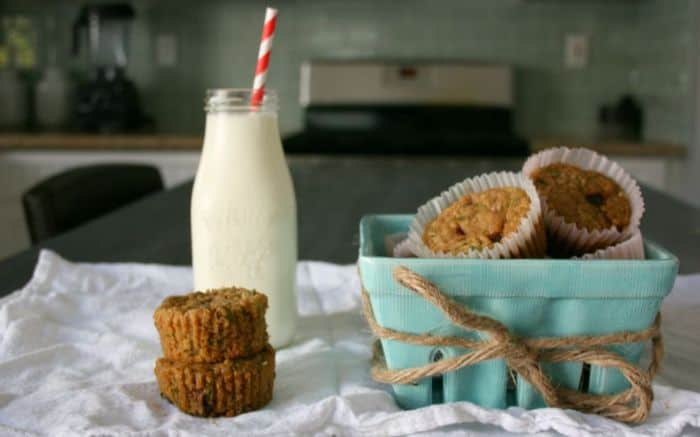 Gluten-Free Zucchini Chocolate Chip Muffins in a blue square bowl with a bottle of milk