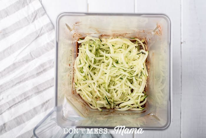 adding shredded zucchini to muffin mix in blender