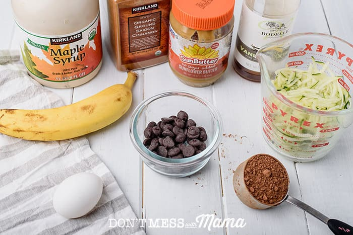 ingredients to make zucchini chocolate muffins like shredded zucchini, chocolate chips, and an egg