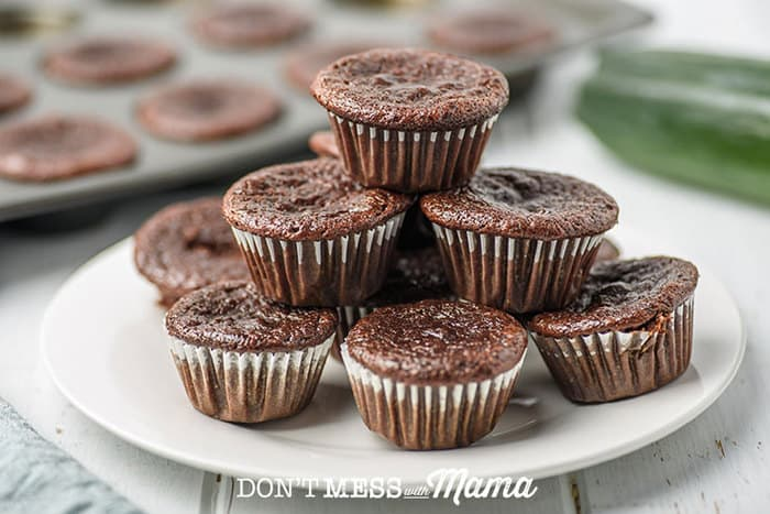 zucchini chocolate muffins stacked on a plate