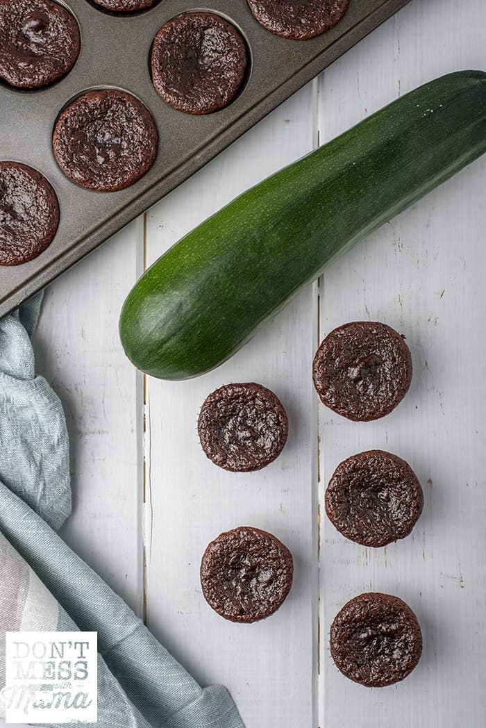 mini zucchini chocolate muffins on a table next to a zucchini and muffin pan