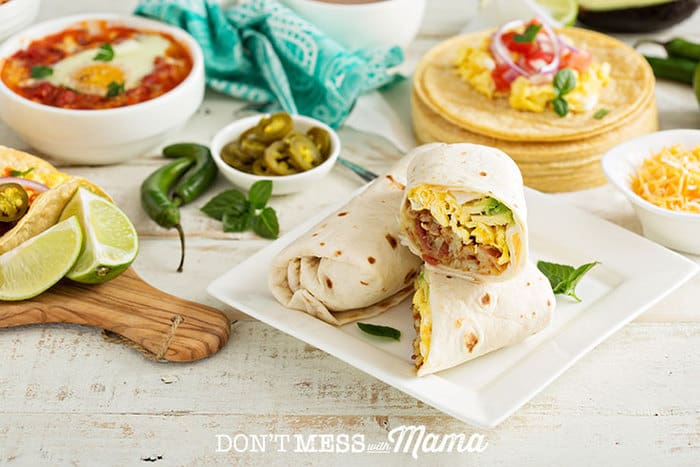 Gluten-free burritos on a plate with salsa and tortillas in the background