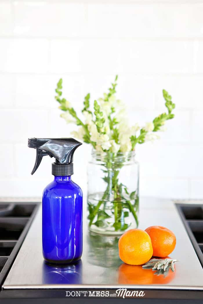 Closeup of glass cleaner, vase of flowers, and oranges on a stovetop