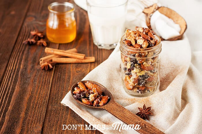 Closeup of nuts and dried fruit in a glass jar and wooden spoon