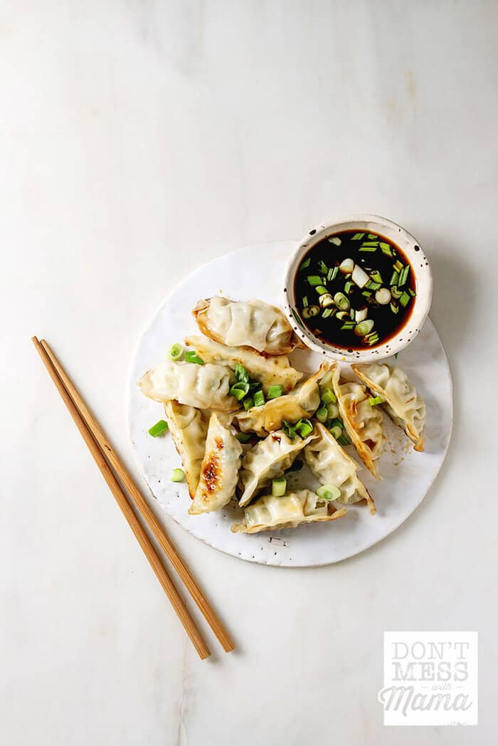 Closeup of gluten free dumplings on a plate with soy sauce in a bowl