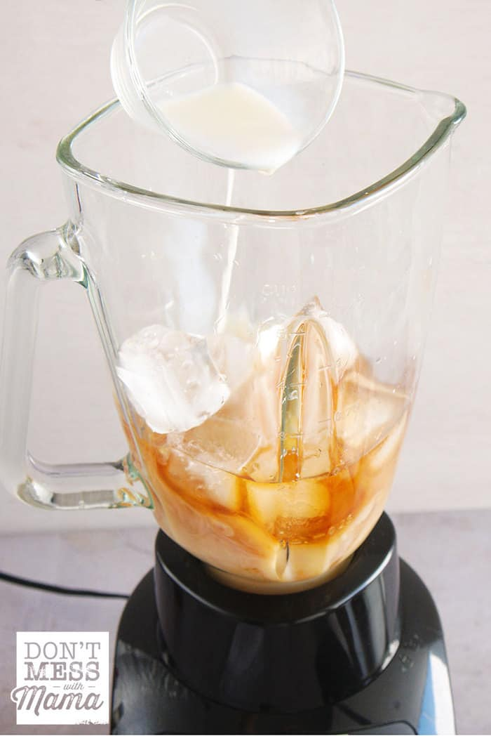 Adding milk to a blender with coffee and ice