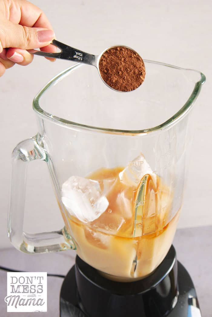 Adding cocoa powder to a blender to make iced coffee