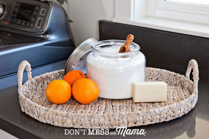 Closeup of DIY laundry detergent with orange and a bar of soap in the background