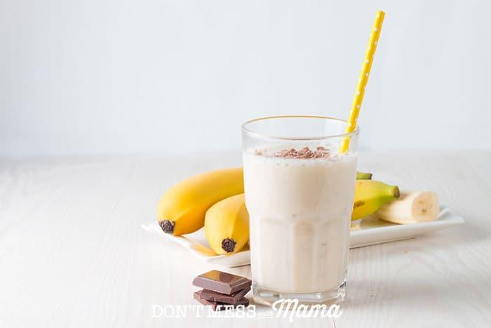 Almond banana smoothie in a glass on a table with bananas and chocolate in the background