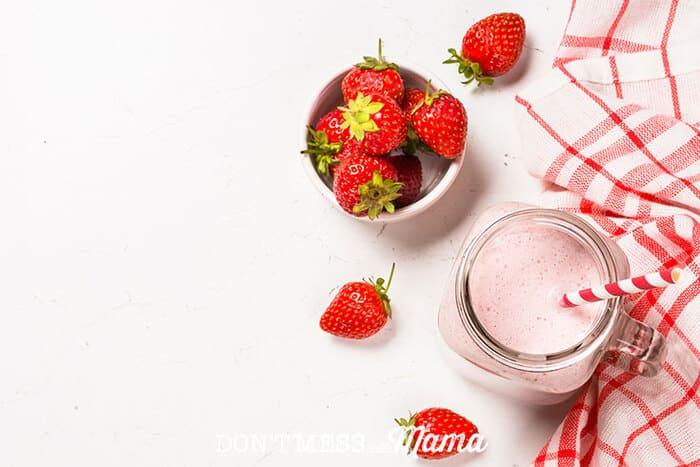 A photo of a pink Magnesium Boosting Smoothie sitting on a table with strawberries next to it