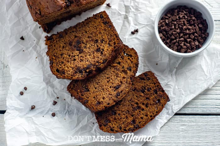 banana bread on parchment paper next to a bowl of chocolate chips