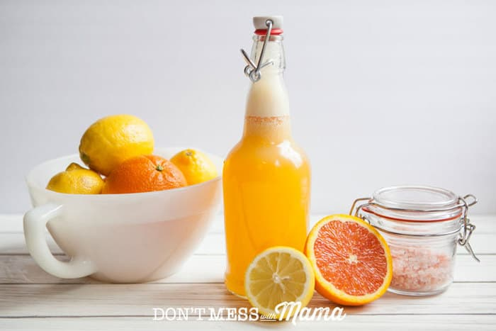 A side shot of a homemade electrolyte drink in a glass bottle on a white surface with citrus fruits