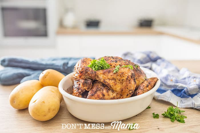 An instant Pot Roast Chicken sitting on a large serving plate garnished with thyme sprigs