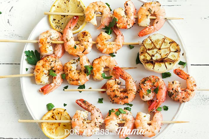 An overhead shot of Lemon Garlic Shrimp Skewers on a white round plate with lemon slices