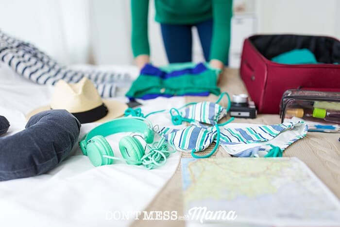 Woman packing for a trip with luggage on a bed