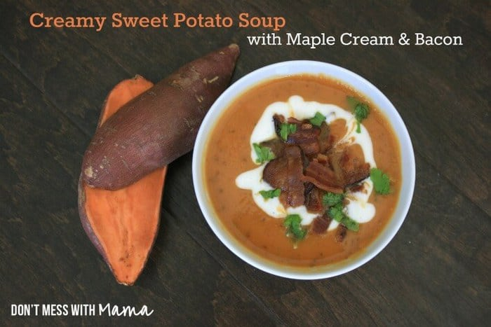Creamy Sweet Potato Soup in a white bowl topped with bacon and cream