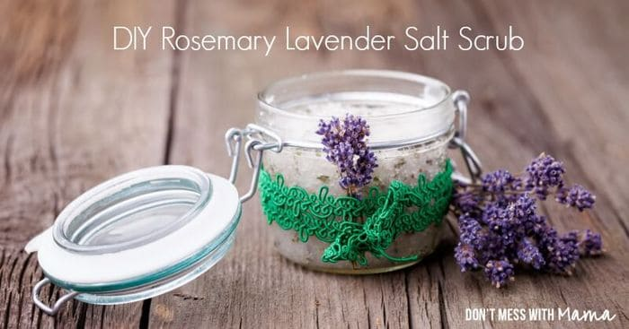 DIY Rosemary Lavender Body Scrub in a glass jar with lavender flowers at the side