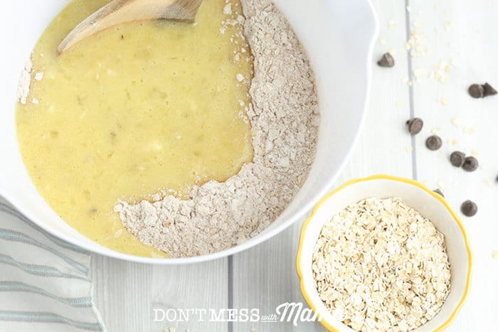 adding beaten eggs to a bowl of flour and oats on a table