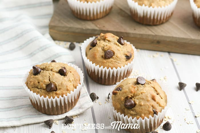 banana chocolate chip muffins on a table with chocolate chips sprinkled around them