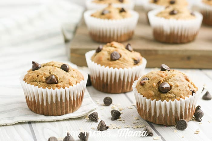 banana chocolate chip muffins on a white table with chocolate chips sprinkled around them
