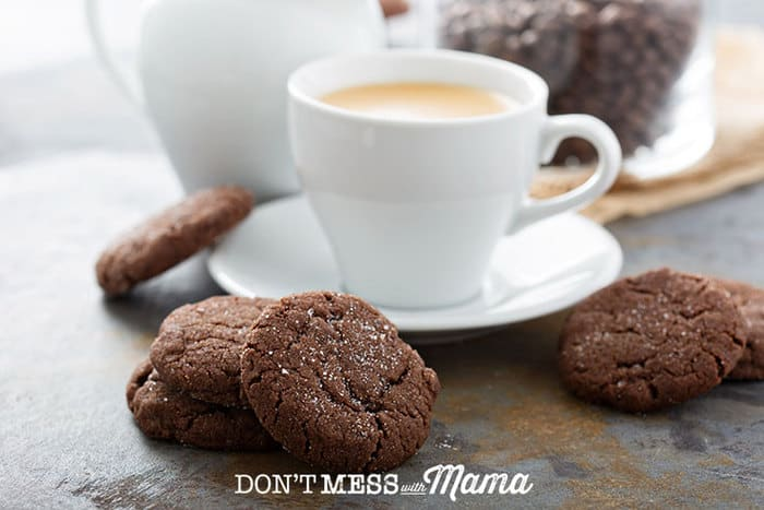 Closeup of chocolate cookies on a table with a cup of coffee in the background