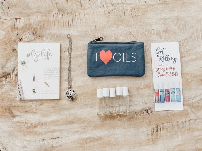 oil recipe book, roller bottles, oil bag, and necklace on a table