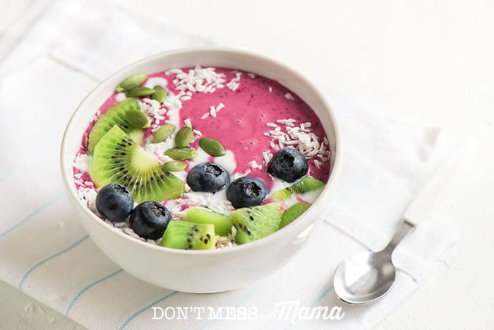Closeup of smoothie bowl with fresh fruit and spoon