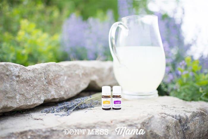 Closeup of lemon and lavender essential oils next to a pitcher of lemonade