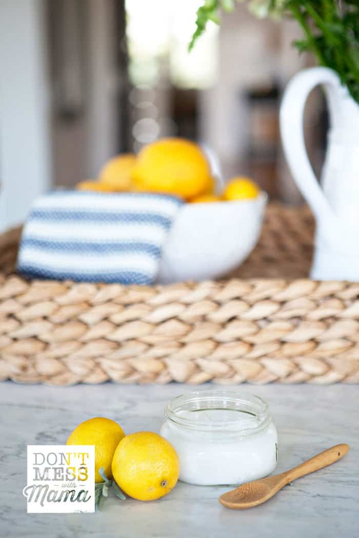 Closeup of a soft scrub cleaner in a jar next to a couple of lemons in a kitchen