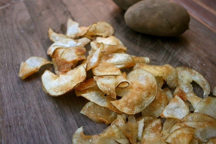 A photo of homemade potato chips on a wooden surface