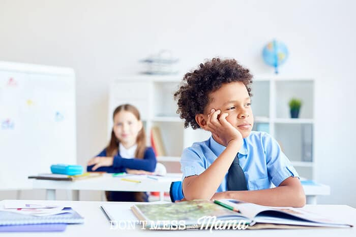 Young boy daydreaming at desk in school