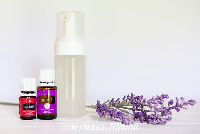 Close up of essential oils, pump bottle of face wash and lavender sprigs