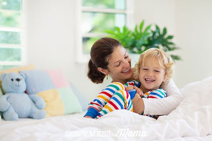 Mom and toddler boy hugging on bed