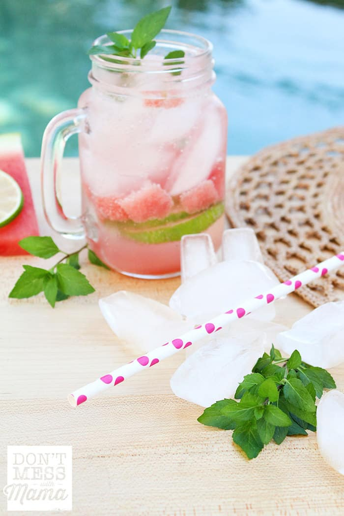 watermelon mojito in a glass with fresh mint and ice on a table
