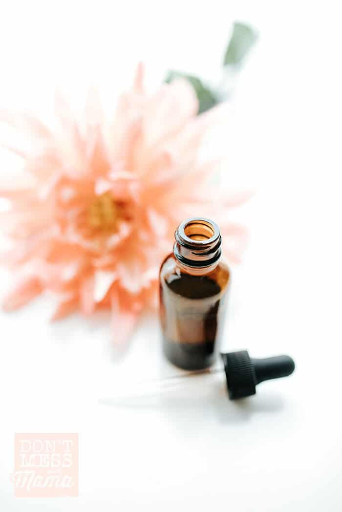 Shot of DIY argan hair oil serum in a glass bottle with a flower in the background