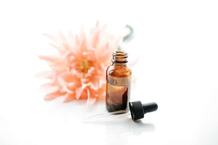 Closeup of DIY argan hair oil serum in a glass bottle with a flower in the background