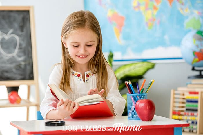 Girl reading a book in a classroom