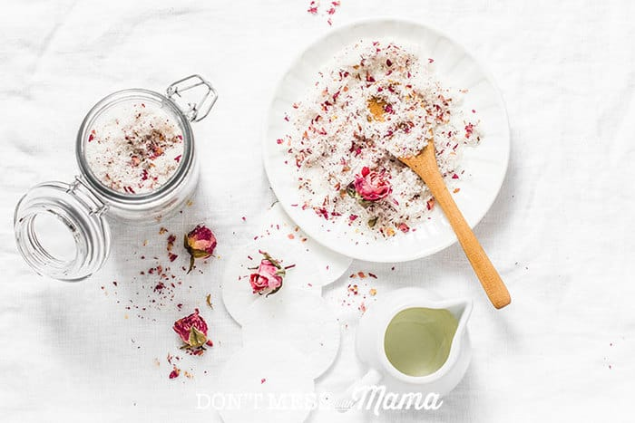 Closeup of homemade bath salts with rose petals in a bowl with a wooden spoon