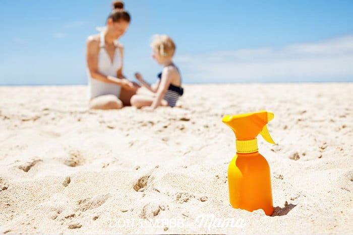 Closeup of sunscreen on the beach with mom and child in the background