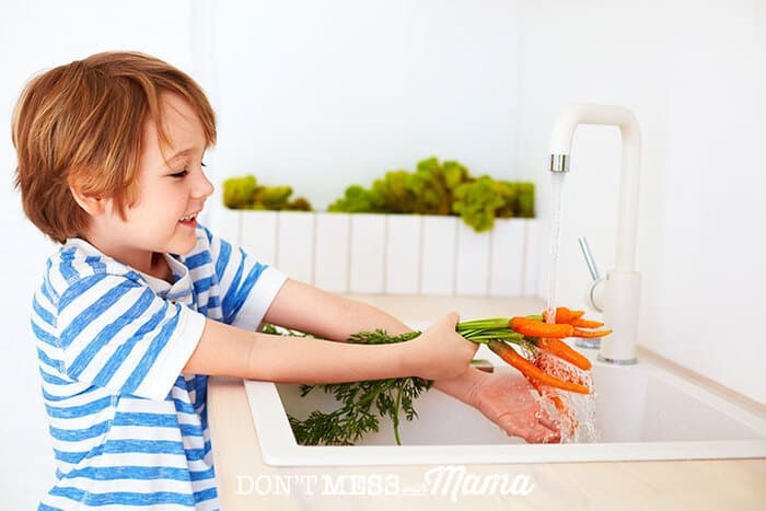 Young boy washing carrots at the sink