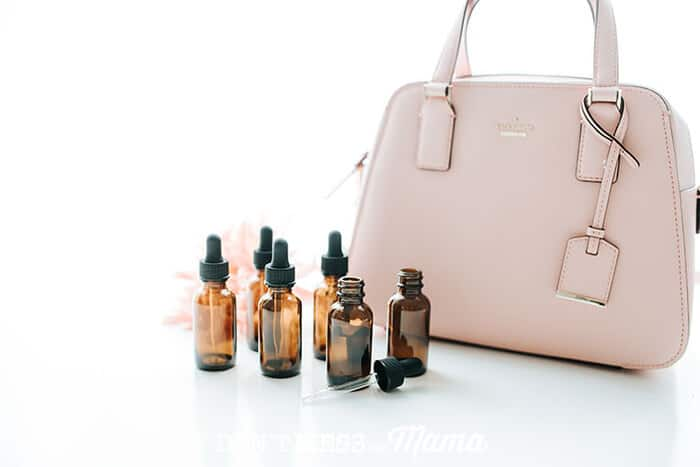 Closeup of essential oil bottle next to a purse