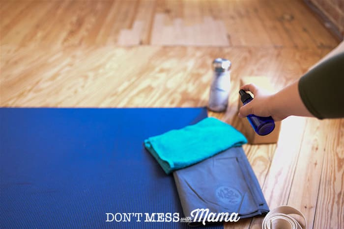 Woman spraying yoga mat with cleaner