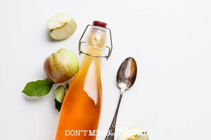 Closeup of apple cider vinegar in a glass bottle on a table with a spoon and apples