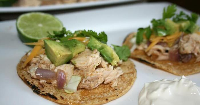 A close up of gluten free lime chicken tacos on a white plate with a slice of lime in the background