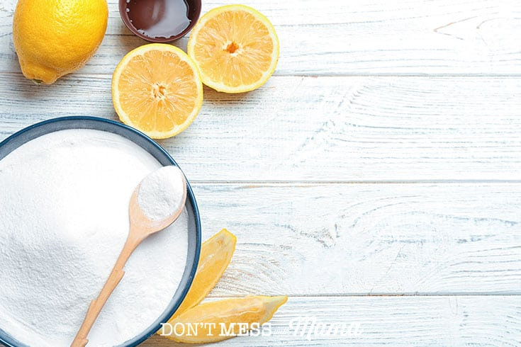 Closeup of baking soda in a bowl next to sliced lemons