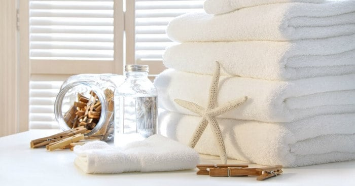 A stack of towels with a clear bottle of cleaning product beside it