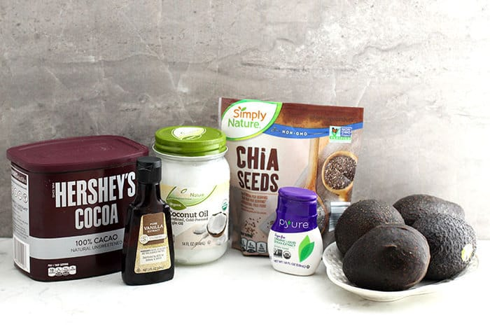 ingredients to make chocolate pudding including cocoa powder, avocados, coconut oil, chia seeds