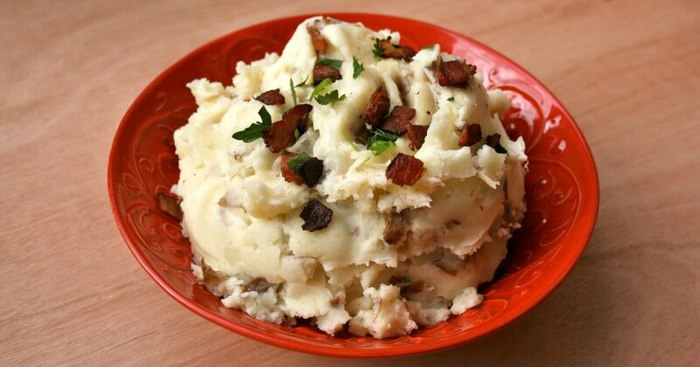 A close up of Paleo mashed potatoes in a red bowl and topped with bacon