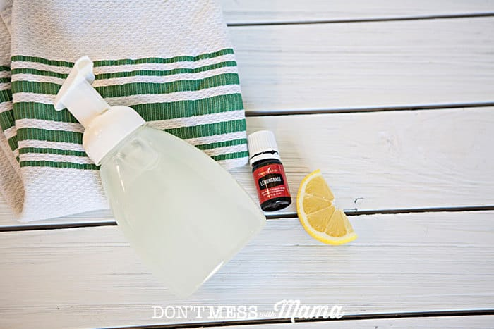 Overview shot of DIY foaming hand soap on a table with a towel and lemongrass essential oil